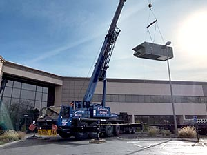 100 ton A/T crane lifting a new air conditioning unit onto the roof of an office building in Westerville, Ohio.
