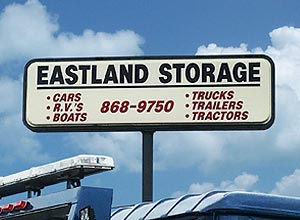 Eastland Crane storage sign above their 20 acre fenced storage lot showing they offer storage for cars, RV's, boats, trucks, trailers, tractors.